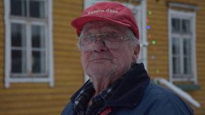 En äldre man med röd keps står utanför ett gult trähus. Vinter och snö.