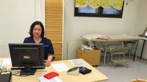 hälsovårdare sitter vid sin dator