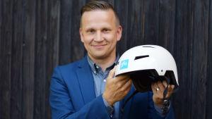 Polisen Mats Sjöholm håller i en vit hjälm. Hjälmen är i fokus.