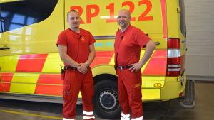 förstavårdarna tomas sundblom och kenneth hed står framför en ambulansbil