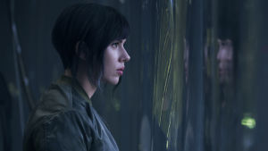 Major (Scarlett Johansson) står invid ett mörkt fönster och ser ut.