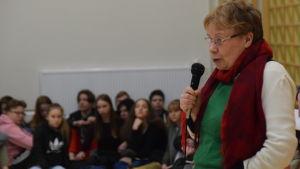 kvinna talar i mikrofon till ungdomar i gymnastiksal