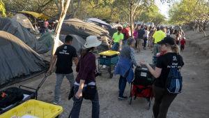 Frivilliga delar ut mat i migrantlägret i Matamoros i Mexico vid gränsen mot USA.