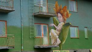 Konstverket på väggen. Ett barn sitter inne i ett kronblad.