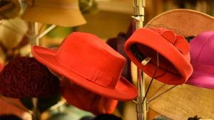 Punaisia, keltaisia ja muita kirkkaan värikkäitä hattuja telineissään näytillä