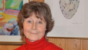 Karin Munsterhjelm, bakom har hon några tavlor.