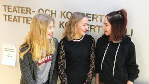Tre flickor framför en skylt