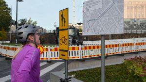 Cyklist tittar på skylt med karta
