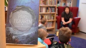 Boken pärlfiskaren i förgrunden, barn och författaren suddigt i bakgrunden.