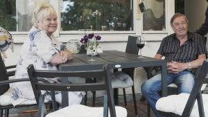 Maritta och Risto Pellava njuter av varsitt glas vin på sin veranda.
