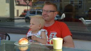 Janne Ylönen sitter vid ett bord och tittar ut mot vägen, han har sitt gudbarn i famnen.