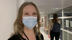 Kvinna med munskydd på står i skolkorridor. Hon ler in i kameran, bakom hennes syns elev gå genom korridoren.