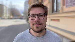 Mansperson i ljusgrå tröja står utanför gulrappad byggnad, ler svagt mot kameran.