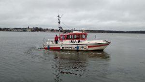 Ekenäs sjöräddares räddningsbåt Ajax i vatten. I bakgrunden ser man Ekenäs centrum.