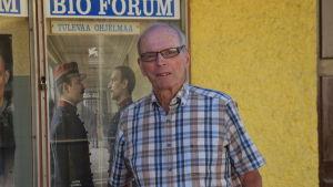 En  äldre man i rutig, kortärmad skjorta står utanför en biograf. I bakgrunden en bioaffisch.