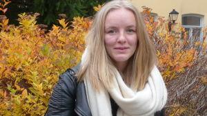 Julia Degerth profilbild, fotat utomhus en lövklädd buske i gula, röda och bruna färger bakom Julia.