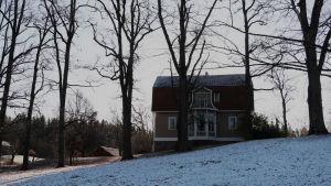 Håkansböle gård bakifrån i skugga med lite snö på marken.