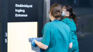 Två läkare med ryggen mot kameran. En av läkarna bär på en låda som ska innehålla coronavaccin.