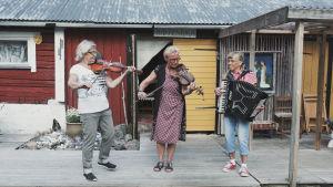Kolme naista soittaa musiikkia, kaksi soittaa viulua ja yksi harmonikkaa kesällä ulkona, taustalla vanha rakennus.