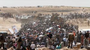Flyktingar från Syrien väntar vid den turkiska gränsen.