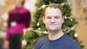 Peter Siegfrids i blå tröja framför en julgran.