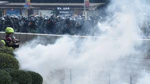 """Kravallpoliser skjuter tårgas mot demonstranter. Ett moln av rök och i bakgrunden en skylt med texten """"Warning tear smoke"""". Polisen anklagas för kriminell brutalitet."""