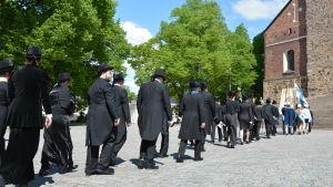 Nypromoverade doktorer vid Åbo Akademi vandrar i procession till gudstjänst i Åbo domkyrka.