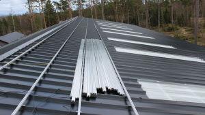 ett svart plåttak med teknik för solpaneler