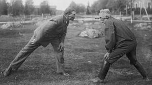 """Två män leker leken """"dra pissmyra"""". Bilden är tagen 1930 i Närpes, Kalaks."""