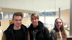Tre elever står i skolaulan