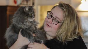 En vit kvinna med blont hår och svarta glasögon ler. och håller upp en långhårig, grå katt.