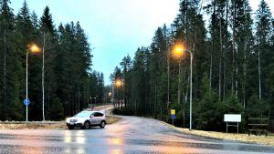 En T-korsning där en bil kör ut bakom en triangel. Det regnar och skymmer. Gatlyktor lyser. Granskog.