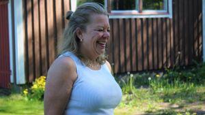 Kvinna i medelåldern klädd i ett vitt linne i somrig miljö ser bort från kameran och skarttar,