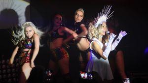 Artister på scenen, sångaren är klädd i vit och har en enorm krona på huvudet.
