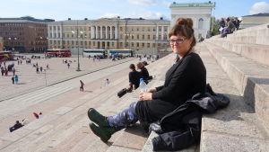Arbetssökande kvinna sitter i Senatstorgets trappor
