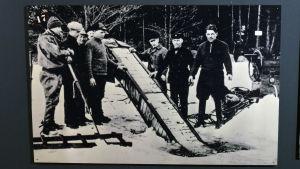 En svartvit bild av en så kallad sprittorped som blir upplyft från en vak i isen.
