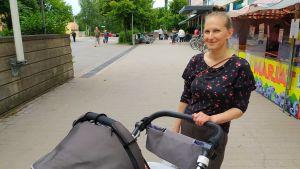Kvinna med barnvagn ute en sommardag.