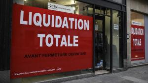 """Skyltfönster täckta med blodröda anslag med texten """"Liquidation totale""""."""