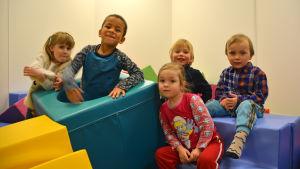 Fem barn i en lekhörna.