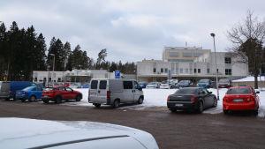 En parkeringsplats med bilar, bakom den synns en stor vit byggnad.