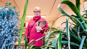 En kvinna i pink tröja står i ett rum med keramikskulpturer på hyllor. Hon  håller en bok i famnen. I förgrunden syns grönväxter.