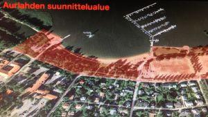 Ett flygfoto över Aurlax i Lojo. Ett område har märkts ut. Där finns en plan på simhall, hotell med mera.