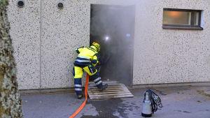 Brandman som jobbar med att pumpa ut vatten.