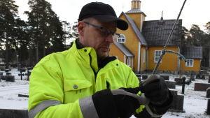 Janne Backas håller i julgransbelysningen, i bakgrunden Dragsfjärds gula träkyrka.