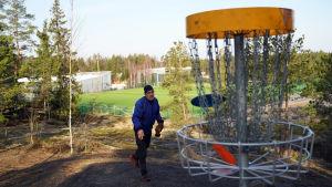 En man kastar frisbeegolf mot en korg som finns uppe på ett berg.