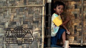 Ett barn tittar ut genom en dörr.