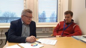 Fullmäktigeordförande Unto Pasanen och kommundirektör Matias Hilden i Puumala förevisar ekonomiska siffror på kommunkansliet.