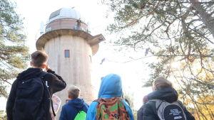 Skolelever tittar upp mot observatorietornet med vit kupol.