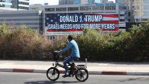 En man i Tel Aviv cyklar förbi en skylt som säger att Israel behöver Donald Trump flera år till.