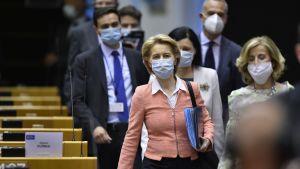 Ursula von der Leyen i grupp där alla bär munskydd, på väg in i mötessal